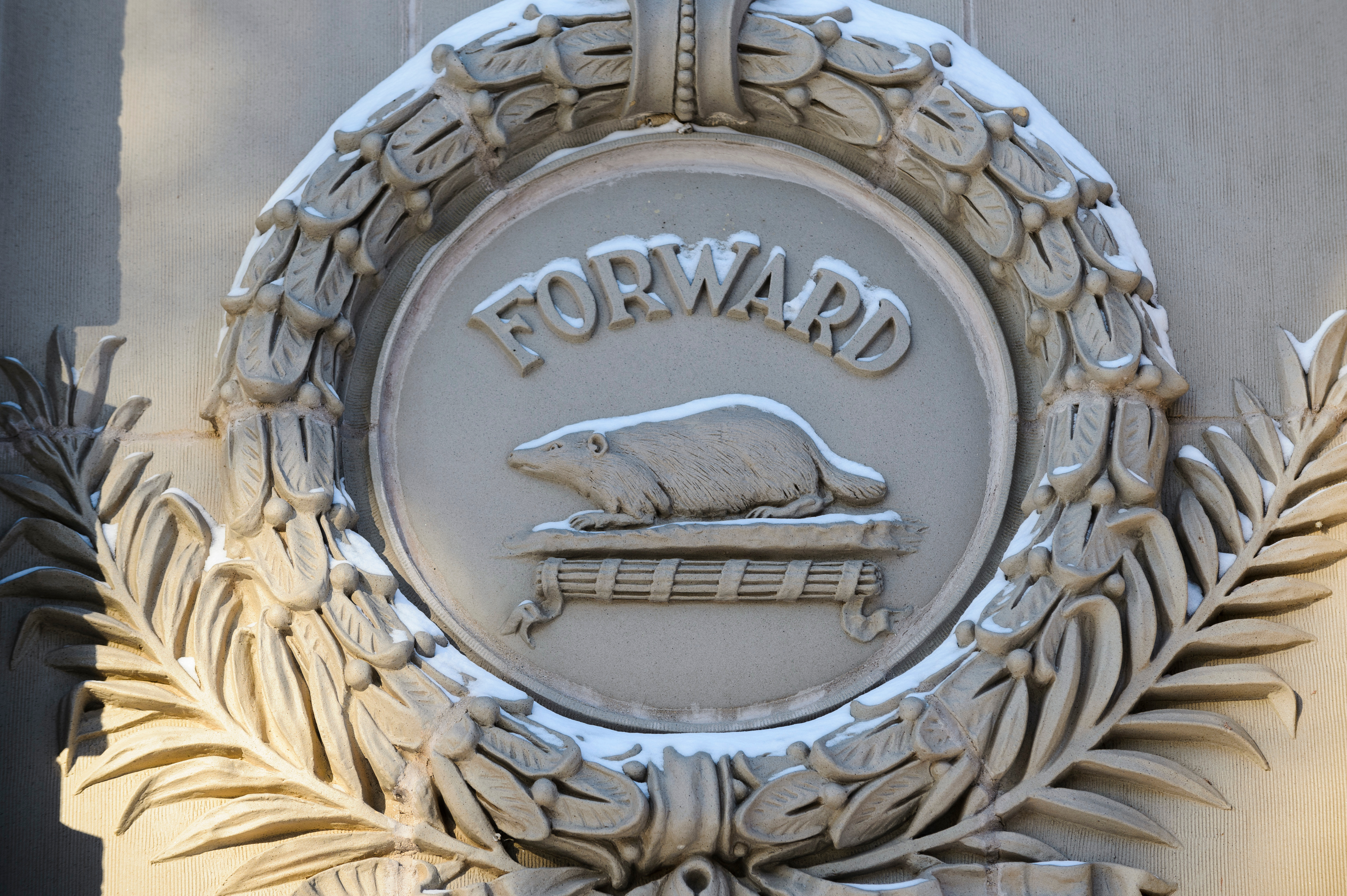 "Architectural detail of a Badger and the word ""Forward"" on the exterior of the Education Building"